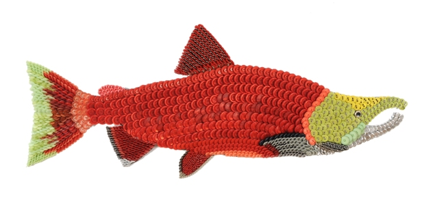 "Smiley: the male SOCKEYE SALMON and all the females migrate to the sea at around one year old as silvery smolts. To avoid predators they allow the river to take them downstream at night, tail first, towards the ocean. The SOCKEYE typically spend two years at sea and then begin their miraculous journey home to their natal streams to spawn. The males fight each other with their hooked noses for dominance. They eventually they die in waters where they began, having completed their circle of life. This is a beautifully noble fish. (45"" W x 19"" H – 15 lbs.)"
